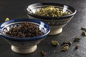 stock photo of cardamom  - two bowls of cardamom and cloves spices on black natural stone - JPG