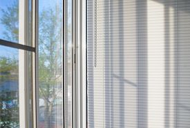 picture of louvers  - closed plastic blinds on the window with the reflection in the glass - JPG