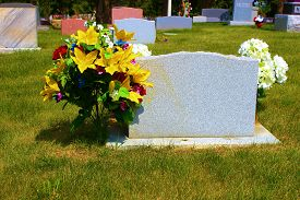 picture of headstones  - Headstone in a cemetery with flowers and surrounded with a manicured green lawn - JPG