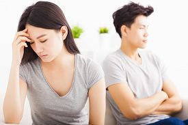 picture of not talking  - young Couple not talking after fight in living room - JPG