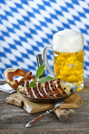 foto of pretzels  - Fried Nuremberg sausages on sauerkraut with a mug of Bavarian beer and a pretzel - JPG