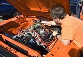 stock photo of carburetor  - mechanic tuning the carburetors on a classic muscle car - JPG
