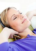 Relaxed woman listen to music lying on a sofa at home