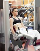 foto of weight-lifting  - Attractive woman lifting weights with a leg press in the room of a sport centre - JPG