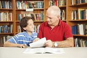 Father or male teacher tutoring a young student in the school library.
