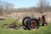 Old aged tractor with equipment in tow