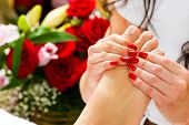 Woman receiving feet massage with massage in a Day Spa; lots of flowers in the background