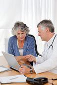 Un médico senior con su paciente mirando el portátil en su oficina