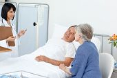 pic of elderly couple  - Nurse talking with a couple in a hospital - JPG
