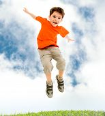 Photo of young boy jumping and raising hands in outside