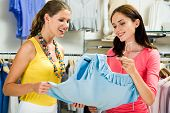 Photo of two pretty women choosing clothes in the store