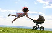 Joyful female jumping over green grassland while holding carriage with baby