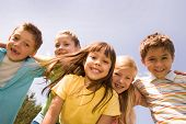 stock photo of school child  - Portrait of happy children embracing each other and laughing with pretty girl in front - JPG