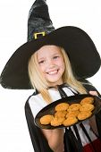 Photo of girl in halloween costume holding tray with bisquits