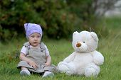 Baby On The Grass With A Bear Toy poster