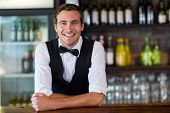 Portrait of happy bartender leaning on bar counter poster