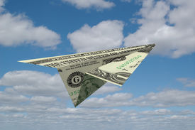 picture of save money  - Paper airplane made out of money with clouds in the background - JPG