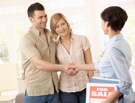 stock photo of real-estate agent  - Estate agent congratulating young couple on making deal on new house - JPG