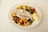 Fish fillet baked with vegetables, Italian dish, on restaurant table shot from above