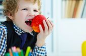 Curly Caucasian Boy With Missing Front Teeth Trying To Bite An Apple. poster