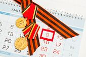 9 May Festive Card - Jubilee Medals Of Great Patriotic War And St George Ribbon Lying On The Calenda poster