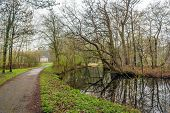 Curved Walking Path In A Dutch Park. At The End Of The Path Is A White Building. It Is Springtime An poster