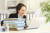 Competent Executive Working Hard Online With A Laptop And A Lot Of Paperwork At Office poster