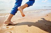 Barefoot child running on sandy beach along coastline while enjoying summer vacation or weekend poster