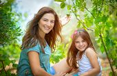 Mother with daughter in the orchard, enjoying the appearance of first fruits, young gardeners with p poster