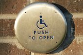 image of physically handicapped  - Handicap push to open button along exterior brick wall - JPG