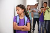 Sad African American girl indoors. Bullying in school poster