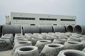Stacked Cement Pipes At Concrete Factory, Outdoors Warehouse . Industrial Production Of Cement Produ poster