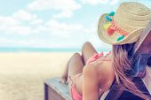 Young Woman Whit Sun Hat Relaxing On Sun Bad Enjoys Sunbath At The Beach With The Sea And Horizon In poster
