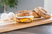 Canadian Bacon, Egg And Cheese Breakfast Sandwich With An Everything Bagel On Cutting Board poster