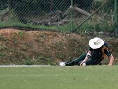 PUCHONG, MALAYSIA - SEPT 24: Jeremy Frith, Guernsey slides to catch the ball in this Pepsi ICC World Cricket League Div 6 finals vs Malaysia at the Kinrara Oval on Sept 24, 2011 in Puchong, Malaysia.