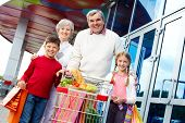 Portrait of happy grandparents and grandchildren with package of food near supermarket