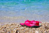 Pair Of Red Swimming Shoes On Marble Pebble Beach Beside Turquoise Sea Water. Summer Holiday Concept poster