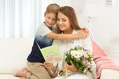 Young woman with her little son and  greeting card for Mothers Day at home poster