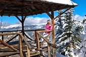 Woman Skier Drinking Tea From Thermos In Open Veranda On Mountain Top. Winter In Canadian Rockies. L poster