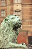 Bronze sculpture of lion against Rosenborg castle, Copenhagen, Denmark
