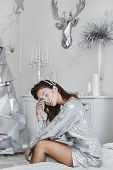 Young Beautiful Woman With Creative Silver Makeup In Silver Dress Posing In Christmas Interior. Fash poster