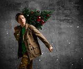 Teenager Man Carrying A Christmas Tree. Young Man In A Jacket Carrying A Christmas Tree Decorated Wi poster