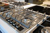Gas stove with stainless steel tray selling in appliance retail store showroom, closeup poster