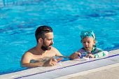 Father Teaches Girl To Swim In The Pool. Happy Father Teaching His Little Daughter To Swim poster