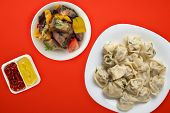 Dumplings On A White Plate On A Red Background. Top View Of Dumplings With Vegetable Salad. Asian Cu poster