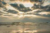 Sunset On Tranquil Beach With Sunbeam And Clouds On Sky poster