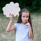 Pretty thinking little girl posing summer nature outdoor with cloud of thoughts (like in comic book) poster