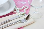 Table setting with fork, knife, plates, beads and napkin