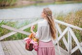 Young Woman Blonde With Long Hair In Retro Style Vintage Clothes Stands With A Picnic Basket On A Wo poster