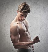 Brawny bare-chested young man showing his biceps